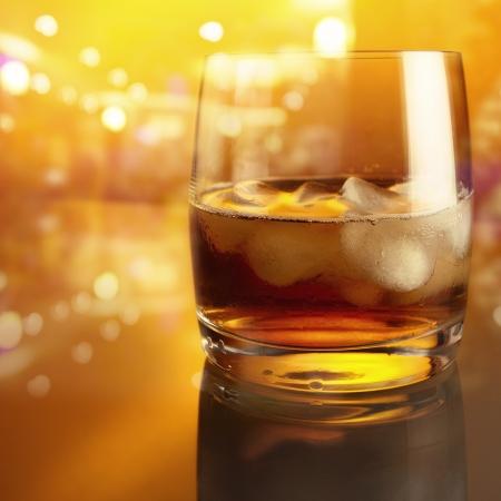 cristallo con whisky su un tavolo di vetro