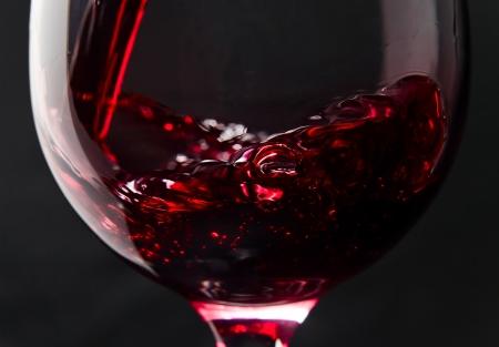 red swirl: Vino rosso in bicchiere di vino su sfondo nero