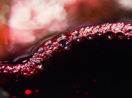 Vino rosso su uno sfondo nero, schizzi astratti