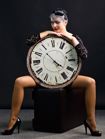 The young beauty in a black hat with old clock photo