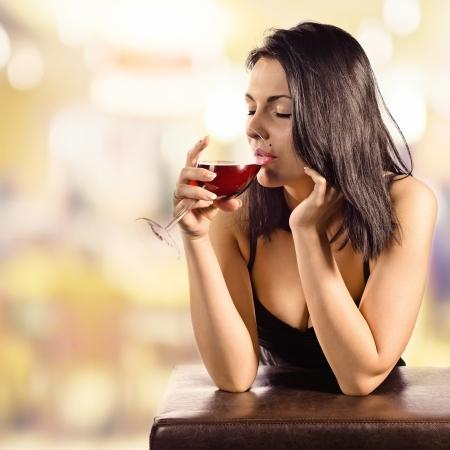jovem mulher bonita no bar com vinho tinto