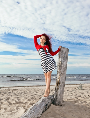 The young girl in striped dress on a beach. Stock Photo - 18941343