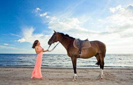 menina bonita no vestido rosa com cavalo no litoral