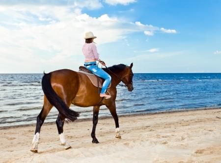 giovane e bella ragazza con il cavallo sul litorale