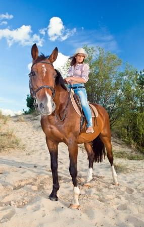 vaqueras: hermosa joven con el caballo en el bosque Foto de archivo