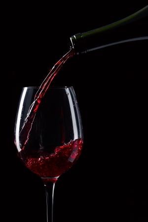 wine pouring: bottiglia e bicchiere di vino rosso su sfondo nero