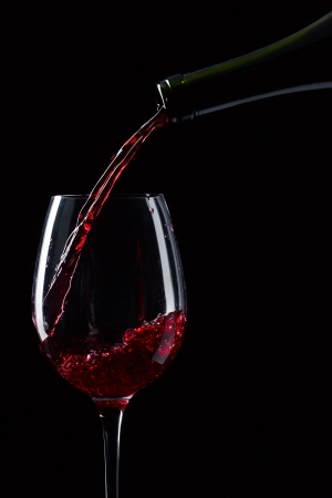 glass of red wine: bottle and glass with red wine on a black background