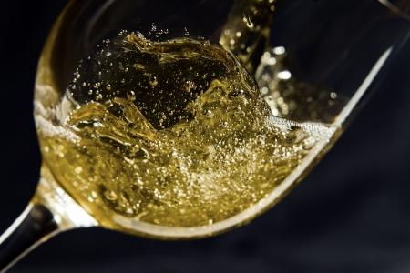 Vino bianco di essere versato in un bicchiere da vino. Archivio Fotografico