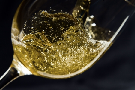 White wine being poured into a wineglass.  Imagens