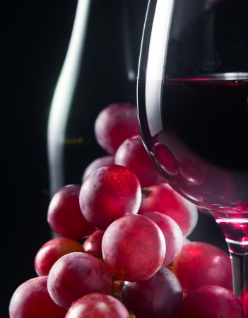 grape and glass with red wine on a black background photo