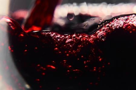 Vino rosso su sfondo nero, schizzi astratti.