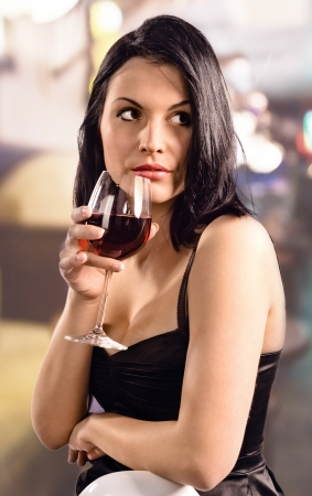young beautiful woman in black dress with red wine  Stock Photo - 19502691