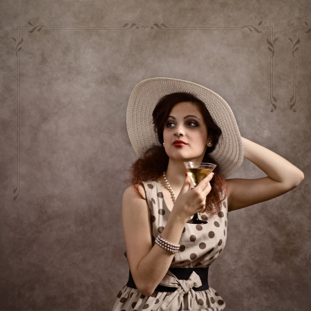 young beautiful woman in  hat with cocktail photo