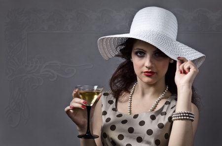 young beautiful woman in hat with martini photo