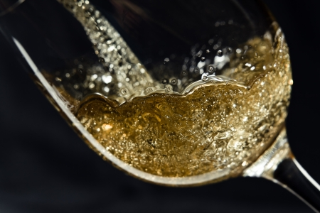 Vinho branco sendo derramado em um copo de vinho.