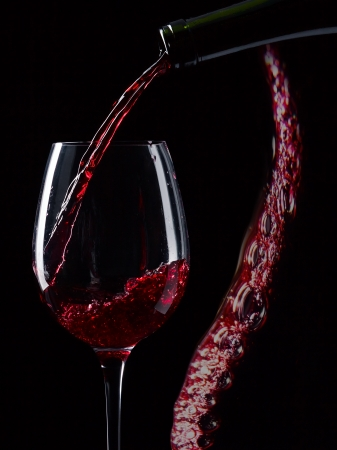 filling bottles: bottle and glass with red wine on a black background