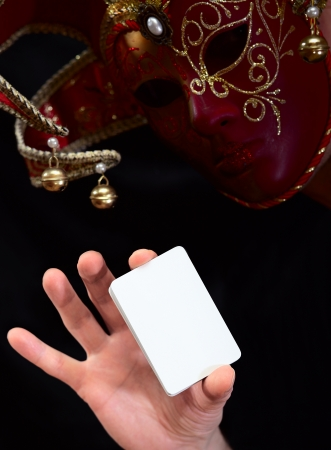 ambiguity: jokerin in mask with white card Stock Photo