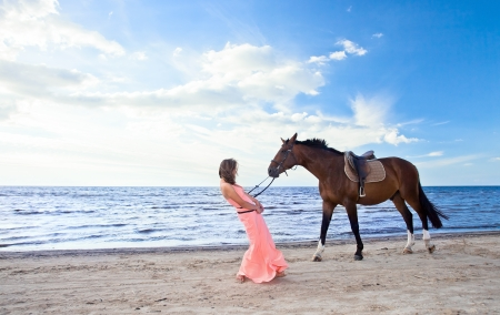 animal sexy: beautiful girl in pink dress with horse on seacoast