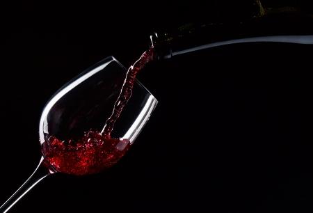 ボトルと黒地に赤ワインのガラス 写真素材