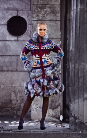 Model in a knitted coat with fur of a fox photo