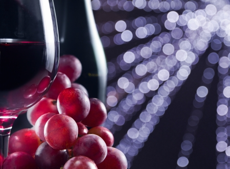 grape and glass with red wine on a black background Imagens