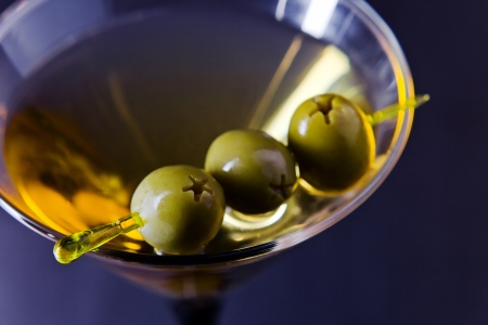 martini with green olives , focus on oliwes