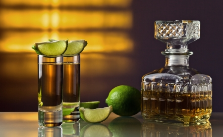 gold tequila and lime on a glass table. photo