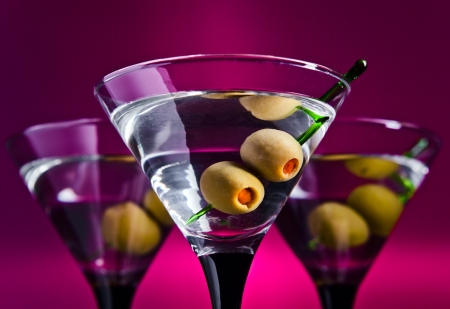 glasses with martini and green olives, focus on olives photo