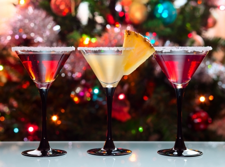Three glasses with cocktails  against a Christmas fur-tree