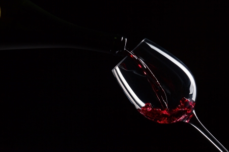 bottle and glass with red wine on a black background Stock Photo - 22967259