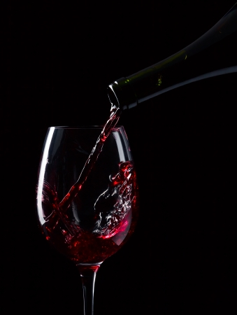 ボトルと、黒の背景に赤ワインのガラス 写真素材
