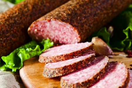smoked sausage with salad on kitchen table photo