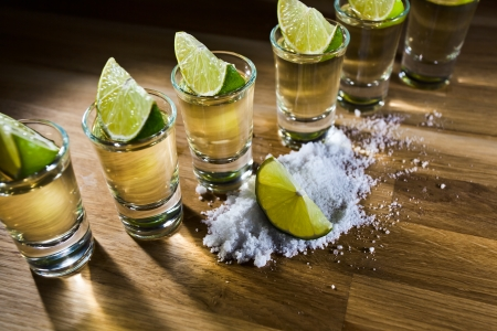 tequila , lime and salt on wooden table Imagens