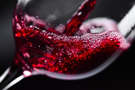 horizontal bar:  Red wine in wineglass on  black background