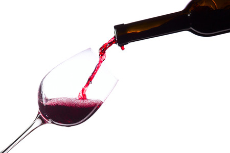 Red wine in wineglass on white background Фото со стока