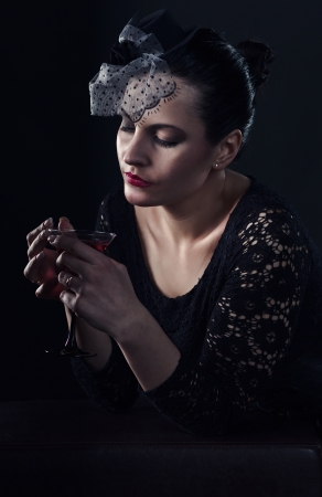 young beautiful woman in black  with cocktail Stock Photo - 23957264