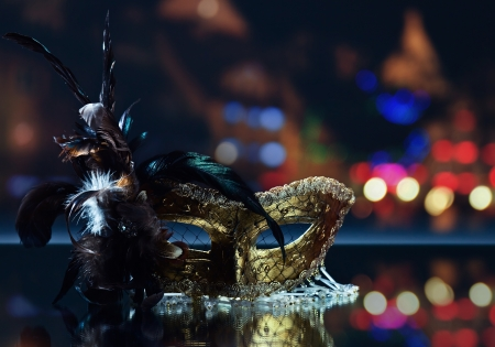 The Venetian mask with feather on  mirror table