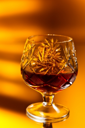 snifter: old snifter with brandy on mirror table Stock Photo