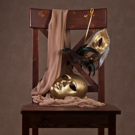 Old gold Venetian masks on a wooden chair photo