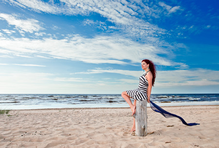 The young woman in striped dress on a beach Stock Photo - 25759195