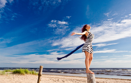 The young woman with blue scarf on a beach. Stock Photo - 25759197