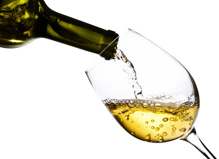 White wine being poured into a wineglass, isolated  on white background,saved clipping path