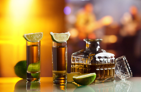 gold tequila and lime on glass table in nightclub photo