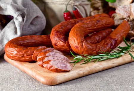 smoked sausage and rosemary on a linen cloth photo