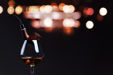 snifter: pipe and snifter with brandy on  dark background Stock Photo