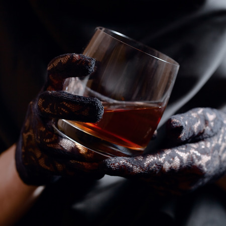 woman in black gloves with glass of whiskey photo