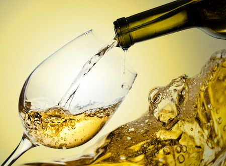 green bottle: White wine being poured into a wineglass Stock Photo