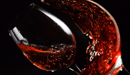 pink wine: pink wine being poured into a wineglass on black background