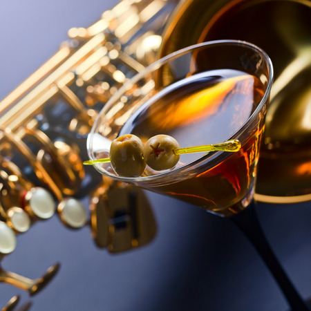 saxophone and martini with green olives , focus on foreground Banco de Imagens