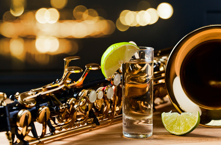 saxophone and tequila with lime on wooden table Standard-Bild